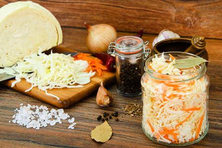 fermenting: Sauerkraut, Carrot, Salt, Water, Fennel Seeds and Pepper on Wood Background Studio Photo