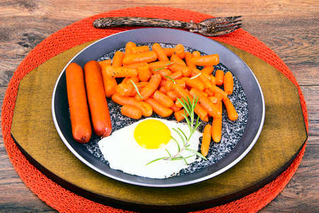 scrambled: Fried Eggs with Fried Sausages and Carrots. Studio Photo Stock Photo