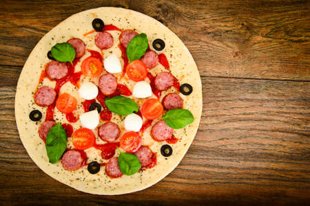 no way out: Raw Pepperoni Pizza with Sausage, Cheese, Mozzarella, Olives and Basil Studio Photo Stock Photo