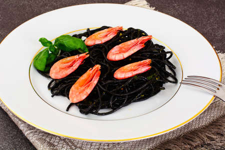 Black Spaghetti with Cuttlefish Ink, Prawns and Basil. Mediterranean and Asian Cuisine. Studio Photo Stock Photo