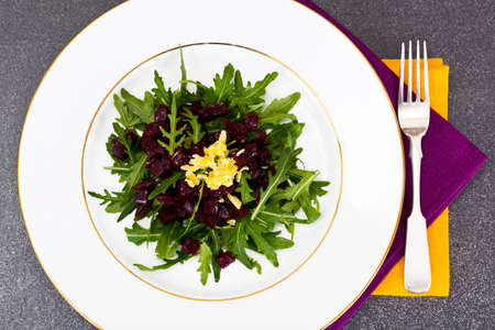 Dietary food without meat: Rocket salad, baked beetroot, cheese and vegetable oil. Studio Photo Stock Photo