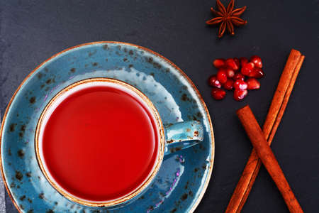 Red Tea with beautiful cup, decorated with cinnamon and pomegranate. Studio Photo Stock Photo