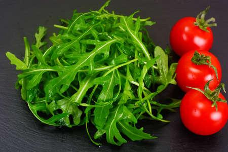 Healthy and diet food: arugula and tomato. Studio Photo