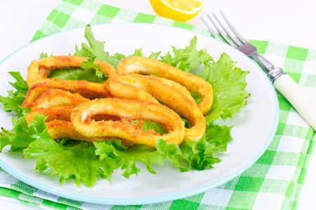 Fried Squid Rings in Breadcrumbs with Lettuce and Lemon Studio Photo