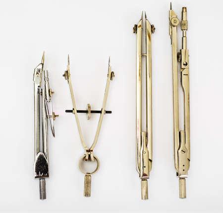 compas de dibujo: Pares de compases y otros instrumentos de dibujo en blanco Foto de archivo