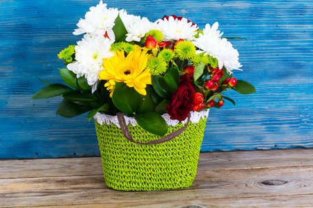 Floral arrangement of fresh flowers in the green wicker basket on old boards. Studio Photo Stock Photo
