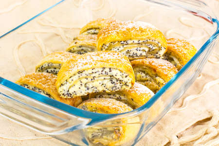 convection: Puff buns with cottage cheese and poppy seeds in a glass baking dish. Studio Photo