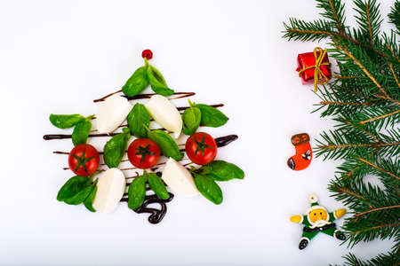 Festive Christmas appetizer caprese salad shaped Christmas tree on white background. Studio Photo Stock Photo