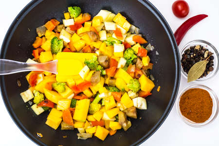 Mix vegetables, stewed in a pan  at home crocheted napkins on a white background. Studio Photo