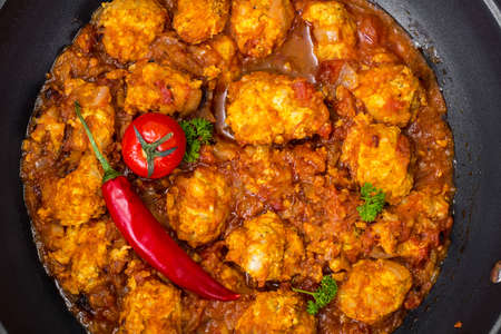 cooked pepper ball: Chicken meatballs with vegetable spicy sauce in the pan. Studio Photo