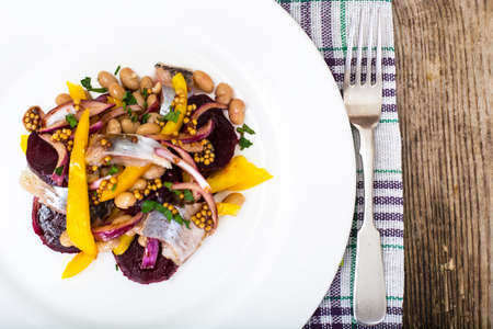 Salad with herring, beetroot, paprika, red onion, mustard and balsamic vinegar. Studio Photo Stock Photo
