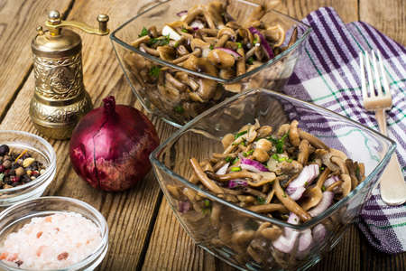Marinated mushrooms and onions in a glass salad bowl. Studio Photo