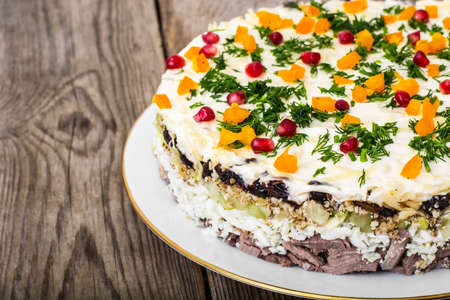 Layered salad with meat and pomegranate seeds. Studio Photo