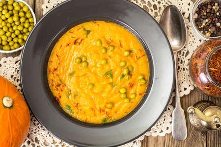 Vegetarian food: vegetable soup with green peas in black plate