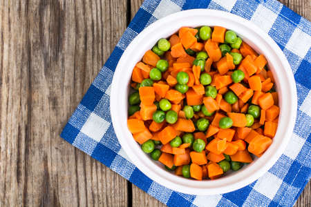 woo: Peas and carrots in a white salad bowl, view from above on a woo