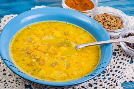 Thick soup of green lentils with curry on a blue background