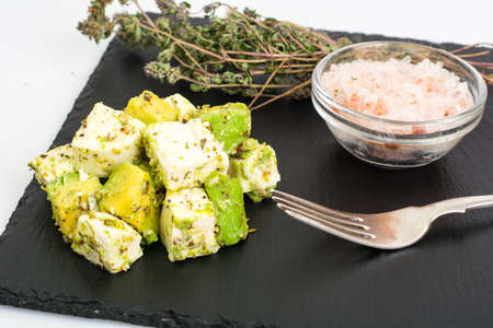 Appetizer with avocado and cheese with herbs on black stone Stock Photo