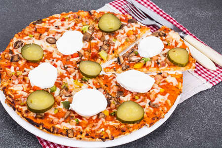 Home pizza with mozzarella and pickled gherkins Stock Photo