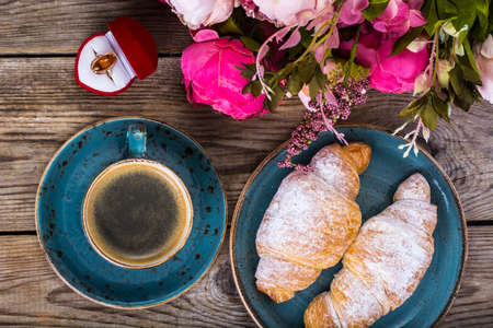 Festive breakfast of espresso, fresh croissant, flowers and gift