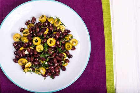 pices: Salad with red beans and green olives in bowl on white boards
