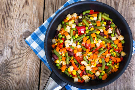Mix of vegetables in frying pan on background of old boards