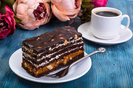 Chocolate sponge cake with caramel and nuts on blue background