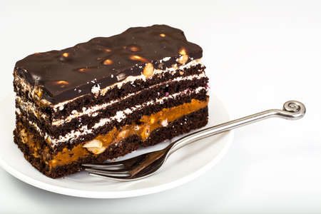 condensed: Chocolate caramel cake with nuts and whipped cream on white back