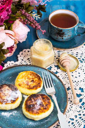 Cottage cheese fritters, honey and tea in a vintage cup on a blu