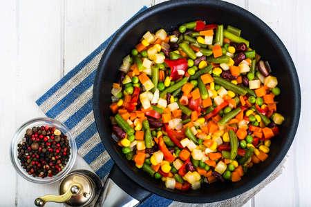 Vegetarian food: vegetables in frying pan on white wooden background. Studio Photo