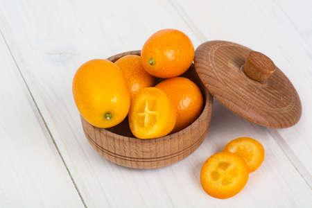Small ripe orange kumquats on white wooden background