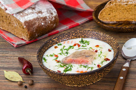 Fish cream soup with salmon in wooden bowl