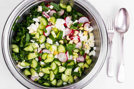 Sliced cucumber, radish, onion, spinach, lettuce and egg in meta
