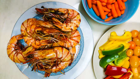 Tiger fried prawns with vegetables on plates