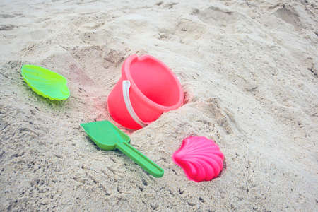Childrens pail and colored molds on the beach in the sand
