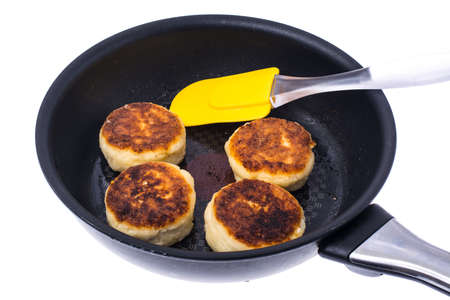Fried cheese cakes in frying pan