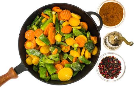 Frozen vegetables in cast-iron frying pan. Studio Photo