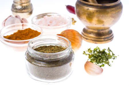 Ground dried herb spices and spices in glass jar. Studio Photo