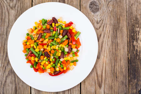 ve: Boiled vegetables in white plate on old wooden table. Healthy ve Stock Photo