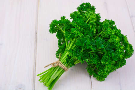 Bunch of fresh parsley on white boards, top view. Stock Photo