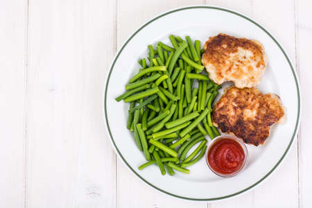 Lunch from green beans and cutlets on white wooden table Stockfoto