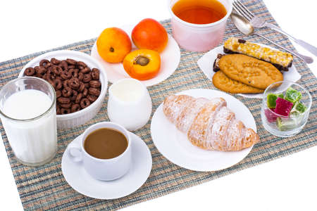 Breakfast table with croissant, muesli, milk, honey and fruits