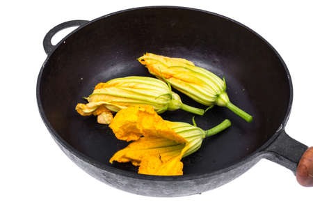 Yellow pumpkin flowers and zucchini in frying pan for cooking