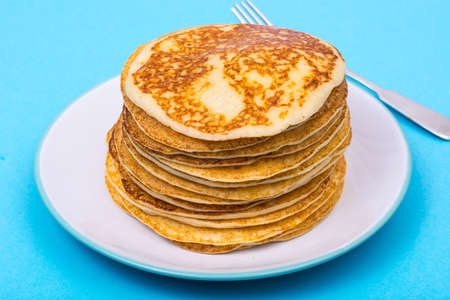 Stack of fresh delicious pancakes on white plate on blue backgro Stock Photo
