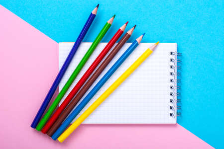 Notepad for notes and colorful pencils on colored background Stock Photo