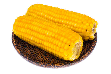 Delicious hot cobs of boiled sweet corn on wooden background. Studio Photo