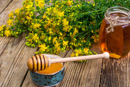 Honey in transparent glass jar and fresh St. Johns wort flowers on rustic background