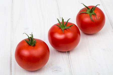 Red tomatoes on white wooden background Stock Photo
