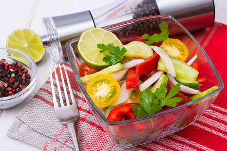 Dietary salad from tomatoes, cucumbers, white onions, lemon, oil Stock Photo