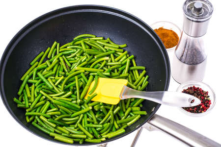 Fried pods of green beans in frying pan