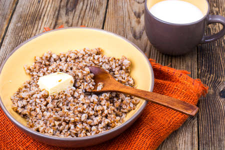 Delicious buckwheat porridge with butter and milk Stock Photo